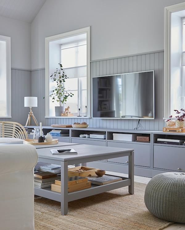 غرفة جلوس حيث تُضفي طاولة التلفاز HAVSTA الرمادية المزودة بقاعدة مع طاولتي قهوة HAVSTA رمادية اللون مظهرًا متناسقًا.