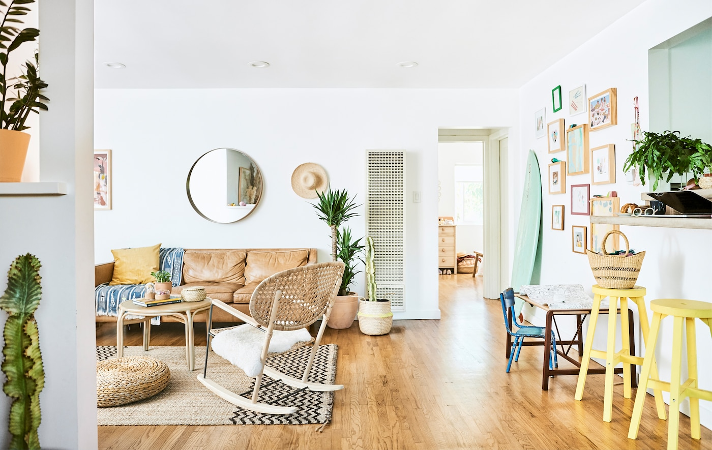 غرفة جلوس مع كنبة جلد، كرسي هزاز من الروطان، سجادة من الخيش، أرضيات خشبية، ومقعدان باللون الأصفر إلى جانب سطح عمل.