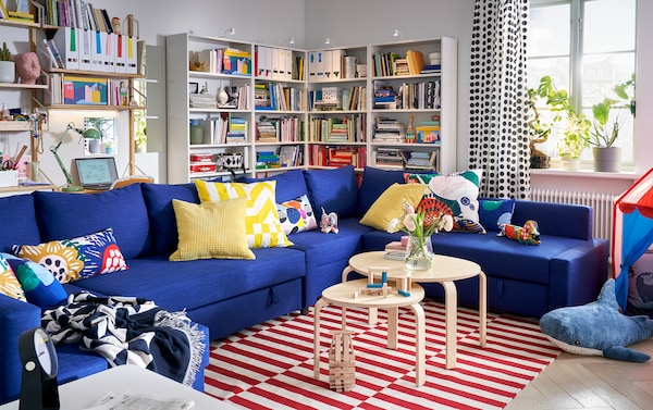 غرفة جلوس مع كنبة سرير زاوية FRIHETEN لون أزرق مع الكثير من المخدات وبعض المكتبات ونافذة مع نباتات على الحافة.