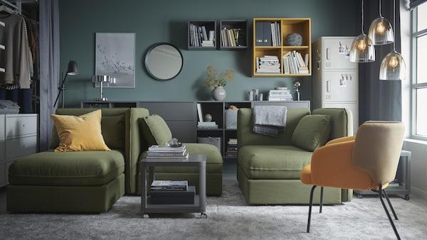 غرفة جلوس مع وحدات صوفات-سرير VALLENTUNA باللون الأخضر، وسجاد كبير رمادي وخزائن باللون الرمادي والأصفر ومصابيح زجاجية معلّقة.