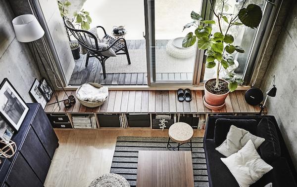 غرفة جلوس رمادي وأسود مع فناء ونوافذ فرنسية.