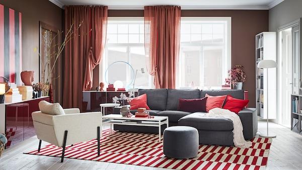 غرفة جلوس تضم ستائر بلون بني-وردي، وسجاد بلون أحمر/أبيض، وصوفا رمادية وخزائن مثبتة على الحائط تتضمن أبواب حمراء فائقة اللمعان.