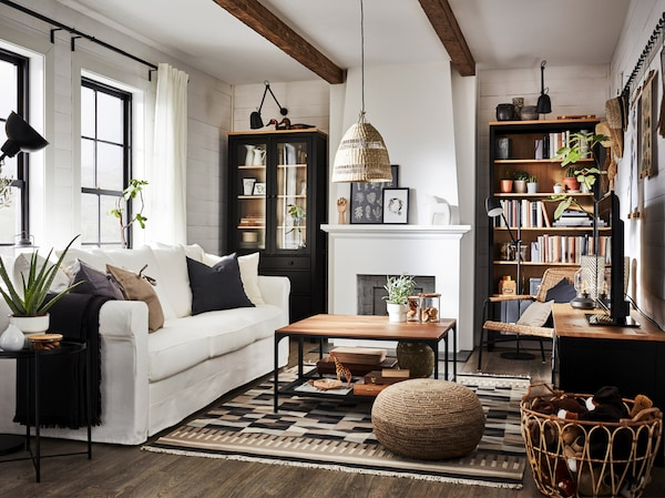 غرفةجلوستقليديةبها مكتبةوطاولة تلفزيون من خشب الصنوبر أسود/بني وكنبة بيضاء وخزانةبباب زجاجي.
