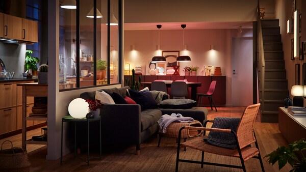 غرفة كبيرة مع مطبخ ومنطقة لتناول الطعام وغرفة معيشة تفصلها عن بعضها مساحات ضيّقة فقط. غرفة مضاءة بمصادر إضاءة متعددة.