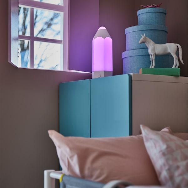 غرفة للأطفال في أجواء مسائية مع صورة عن قرب لدولاب ملابس أزرق ومصباح طاولة PELARBOJ يعطي توهجًا أرجوانيًا.