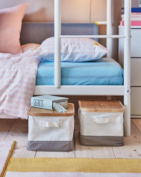 غرفة للأطفال حيث يتم سحب صناديق RABBLA مع أغطية الخيزران من السرير السفلي لسرير بطابقين أبيض.