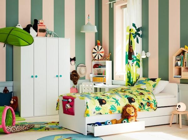 غرفة للأطفال مستوحاة من طبيعة الغابات مع هيكلل سرير أبيض، ودمى طرية، ومنسوجات خضراء عليها طبعات حيوانات مع مظلة على شكل ورقة شجر.