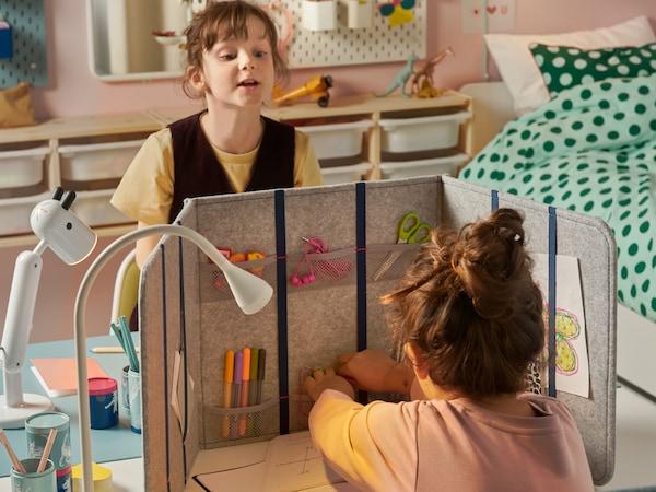 غرفة نوم أطفال بها طفلان في مواجهة بعضهما البعض على جوانب متقابلة من مكتب مقسم بمقسم مكتب ÖVNING.