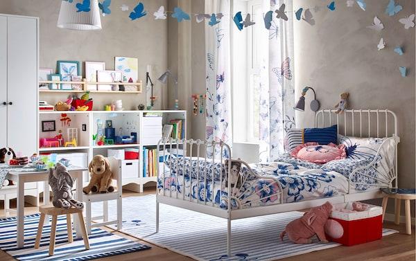 غرفة نوم أطفال كبيرة بها هيكل سرير أبيض وشراشف سرير زهور SÅNGLÄRKA وستائر فراشات أزرق ووردي.
