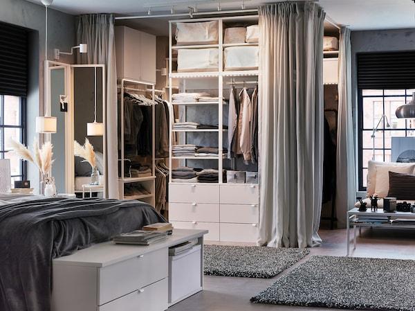 غرفة نوم باللونين الأبيض والرمادي كلها مع هيكل سرير أبيض وخزانة ملابس مفتوحة وستائر رمادية فاتحة وسجاد رمادي داكن.