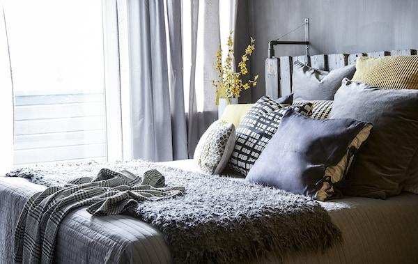 غرفة نوم بديكور رمادي ووسائد صفراء.