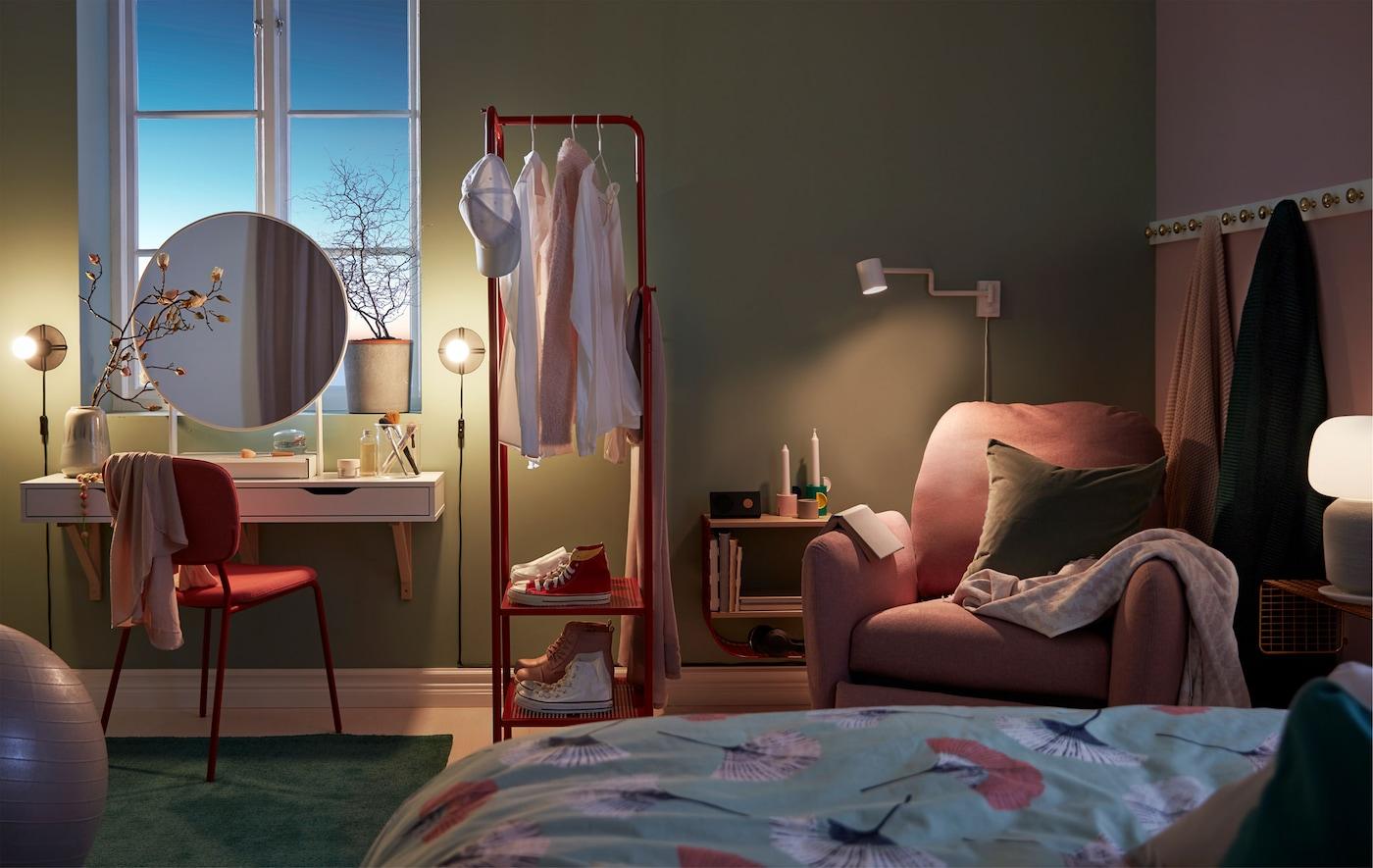غرفة نوم خافتة الإضاءة بها زاوية ماكياج، وعلاقة ملابس مقسمة للغرفة وزاوية قراءة مع كرسي بظهر متحرك.