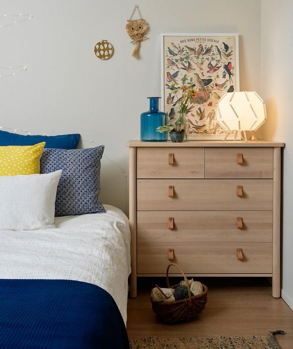 غرفة نوم مع خزانة ذات أدراج خشبية شاحبة وسرير عليه أغطية زرقاء وبيضاء.