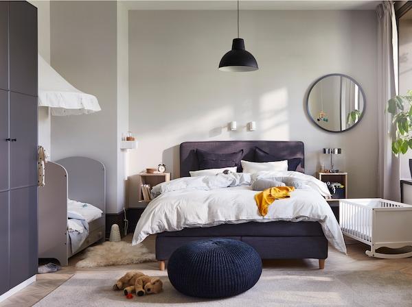غرفة نوم مع سرير أطفال رمادي، وسرير رُضع أبيض، وسرير طويل رمادي، ومقعد أزرق داكن ومرآة مستديرة ومصابيح حائط بيضاء.