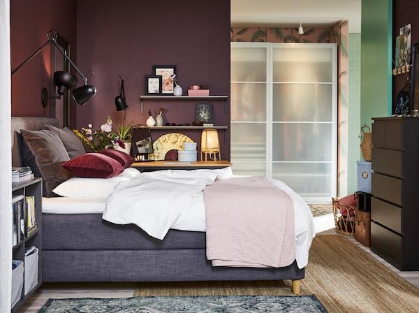 غرفة نوم مع سرير طويل رمادي داكن ومصابيح حائط سوداء وسجادة من الجوت وخزانة ذات أدراج باللونين الأسود والبني وأغطية وسادة حمراء داكنة.