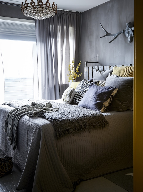غرفة نوم رمادي بها زهور ووسائد صفراء.