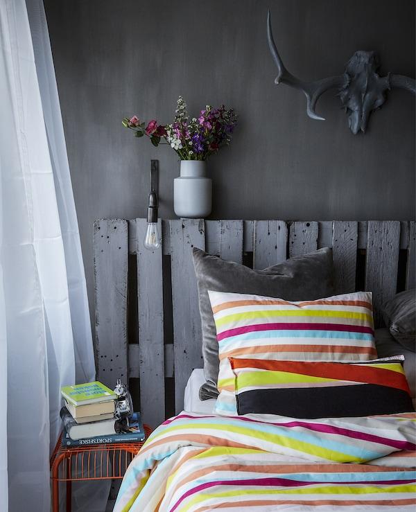غرفة نوم رمادي وأغطية سرير زاهية الألون ومقعد برتقالي.