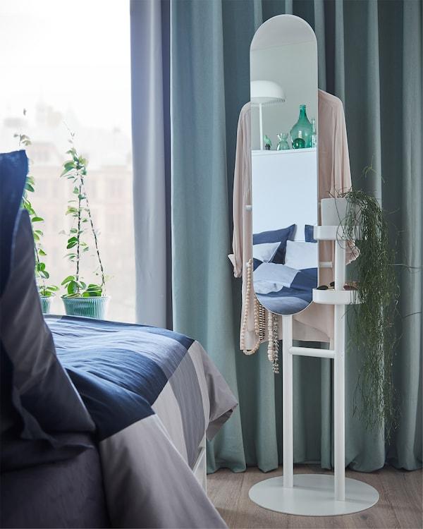 غرفة نوم رمادية/خضراء مع مشجب ملابس أبيض مع مرآة موضوعة في زاوية أمام ستائر خضراء.