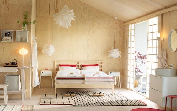 غرفة نوم صنوبر بها هيكل سرير TARVA من خشب الصنوبر لفردين، وطاولتين جانبيتين للسرير لون أبيض وأغطية سرير أحمر وأبيض.