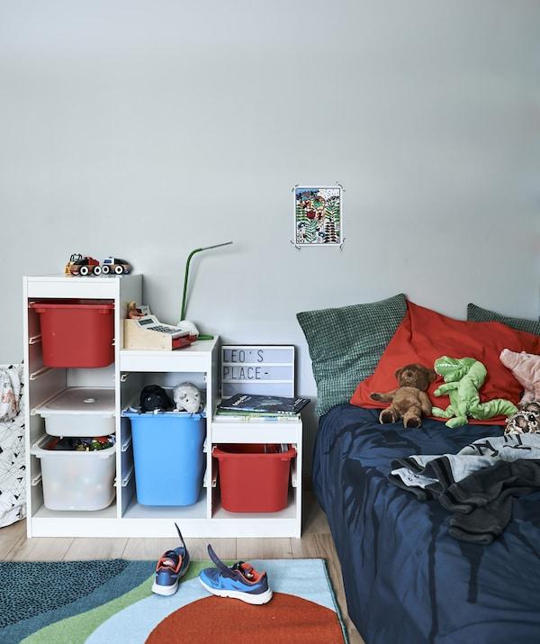 غرفة نوم طفل مع وحدات تخزين وسجاد وسرير ووسائد وألعاب بألوان زاهية.