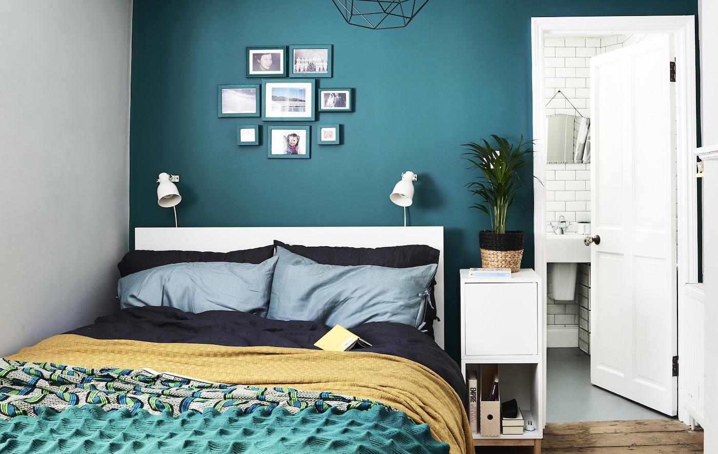 غرفة نوم ذات جدار أخضر داكن ومفروشات سرير زاهية الألوان.