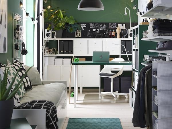 غرفةصغيرةخضراءكلها بها طاولةخضراء، ووحدات رفوفبيضاء، وسرير نهاري، ودولاب ملابس مفتوحة ومصباحمعلقأسود.