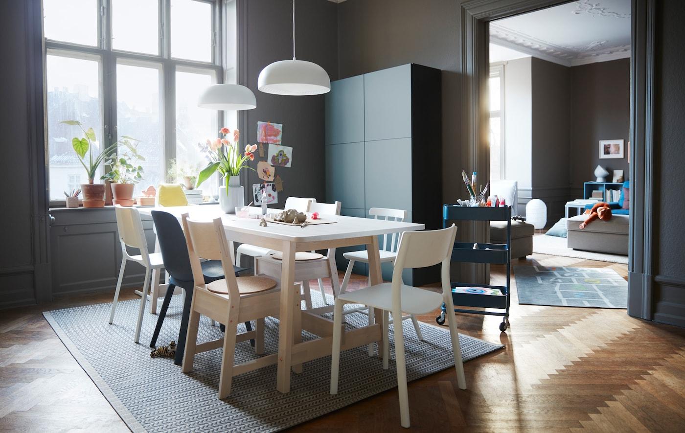 غرفة طعام مع كراسي متعددة الألوان حول طاولة مغطاة بالأبيض وتشكيلة تخزين BESTÅ من ايكيا بلون رمادي/فيروزي.