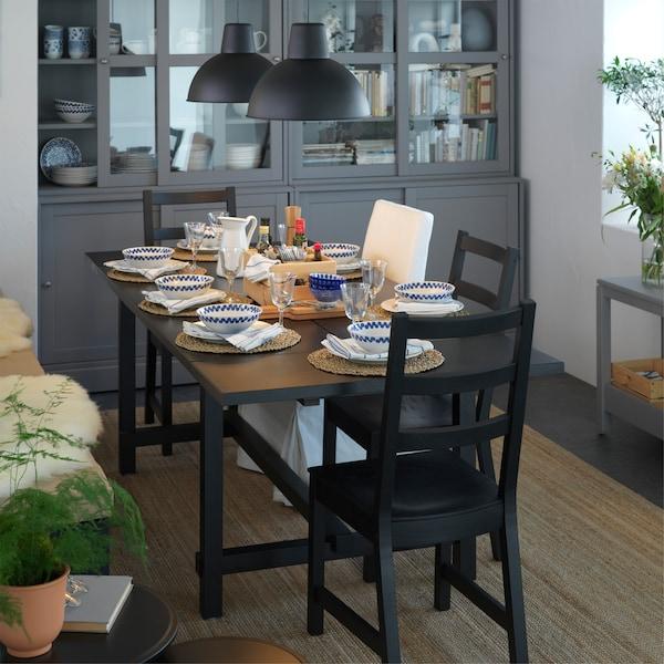 غرفة طعام مع طاولة قابلة للتمديد وكراسي باللون الأسود. تم ترتيب  الطاولة لوقت العشاء، وتعليق اثنين من المصابيح المعلّقة السوداء فوقها.