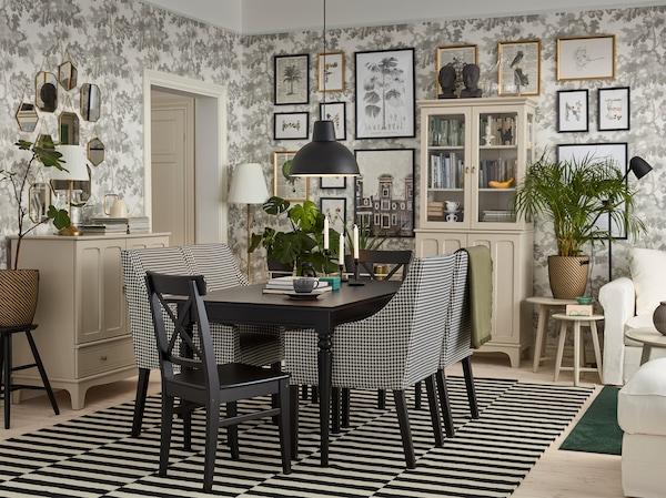 غرفة طعام تقليدية بها طاولة سوداء وخزائن بلون بيج فاتح وكراسي سوداء/بيضاء مع مساند للذراعين وسجادة مخططة.