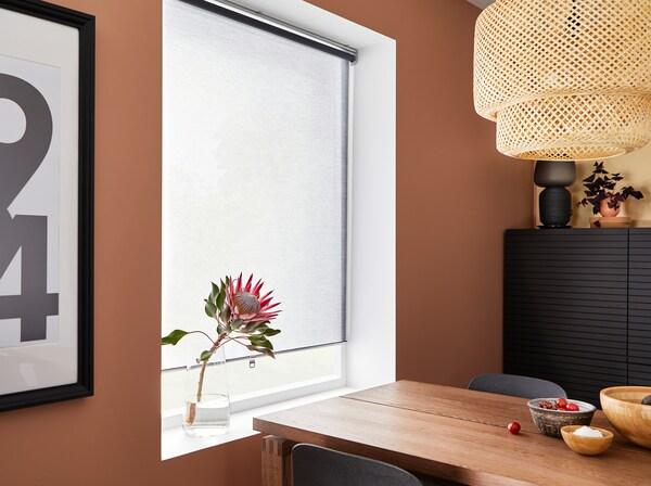 غرفة طعام وردية داكنة مع ستارة لفافة رمادية، ومصباح معلق من الخيزران وطاولة من قشرة خشب البلوط المطلي بالبني.