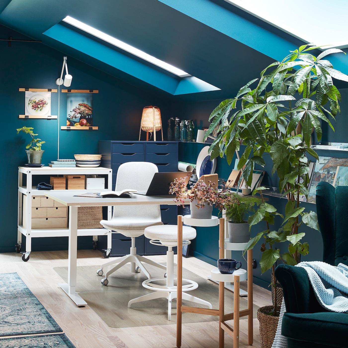 غرفة تضم مكتبًا وكرسي دوار وكرسي أبيض يدعم الجلوس/الوقوف ونباتات خضراء على حامل نباتات وكرسي بظهر مرتفع وجوانب بارزة أخضر اللون.