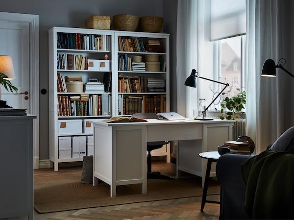 غرفة تحتوي على مكتب أبيض موضوع في الوسط، تتوافق ومكتبات طويلة متوافقة معه خلف كرسي المكتب، ومصباح عمل أخضر على المكتب.