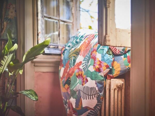 غطاء اللحاف SKOGSFIBBLA بنقش ملون مبيض بواسطة الشمس على نافذة قديمة مفتوحة وموضوعة فوق المشعاع.