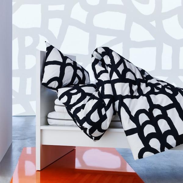 غطاء لحاف وغطاء مخدة SKUGGBRÄCKA بنقوش جرافيك أسود وأبيض مميزة.