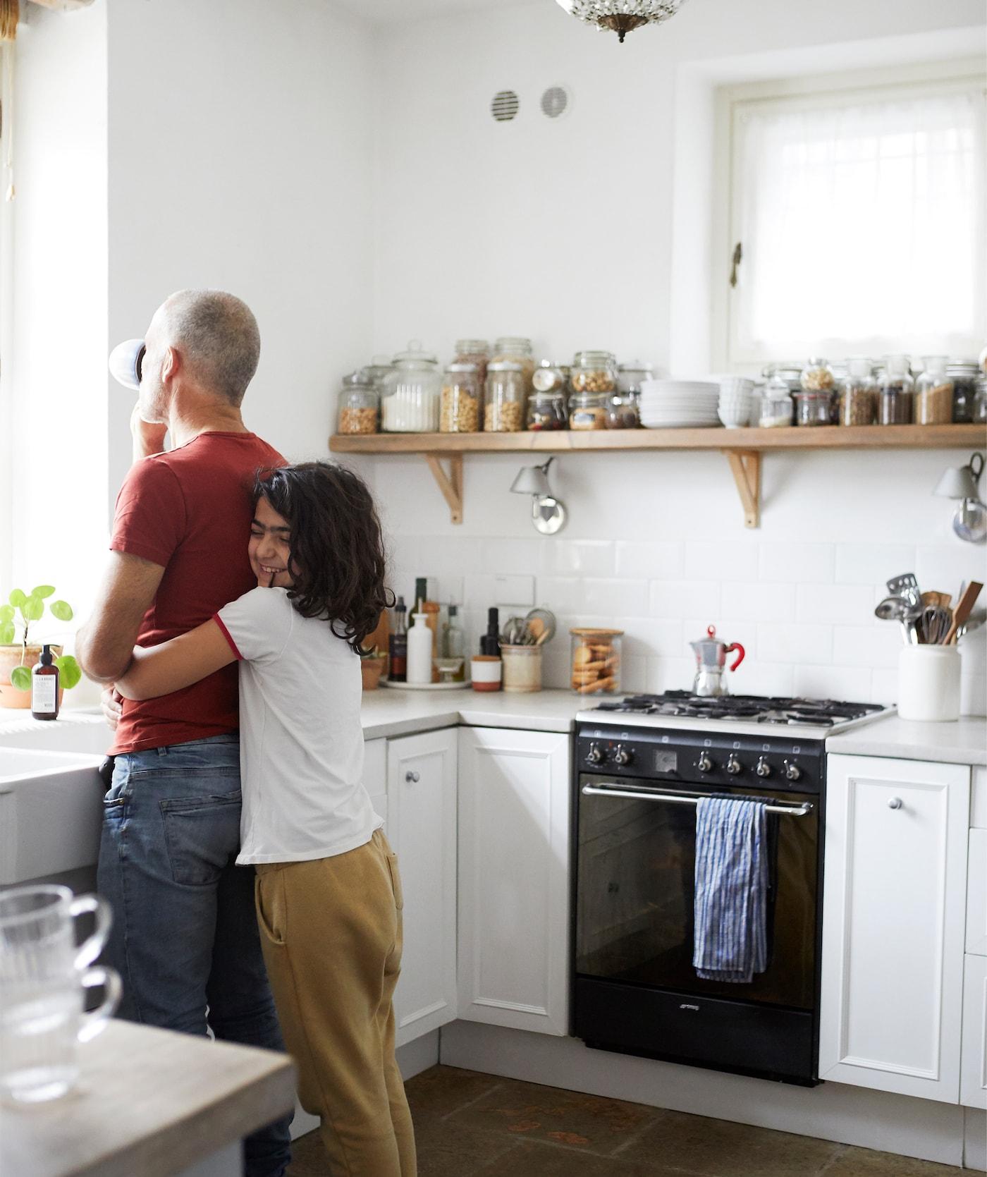 Gigi et sa fille enlacés dans une cuisine blanche avec des murs carrelés blancs et des bocaux placés sur une grande tablette en bois.