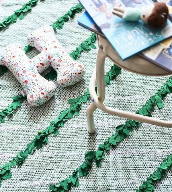 Giochi appoggiati su uno sgabello color crema sopra un tappeto verde – IKEA