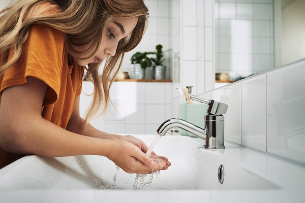Girl cupping flowing water from a PILKÅN bathroom faucet.