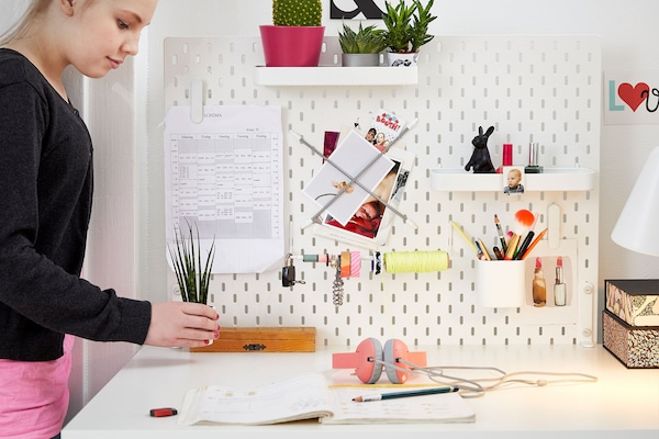 Girl placing small plant onto white desk with a white peg board filled with pens and supplies
