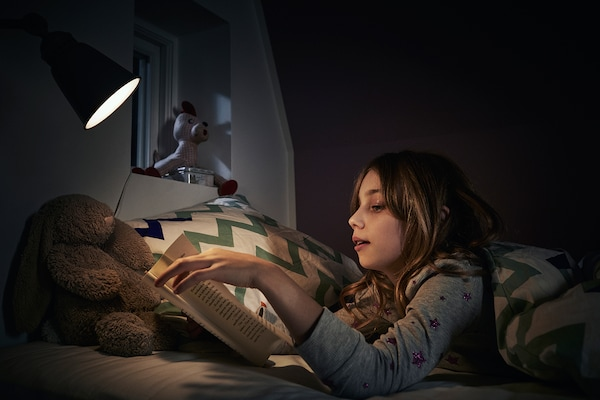 Girl wearing pyjamas reading a book in bed using a small lamp.
