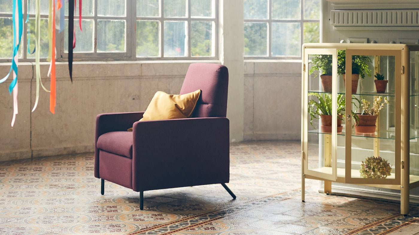 GISTAD recliner in a dark red color with a yellow cushion placed in its seat, standing in a room with big windows.