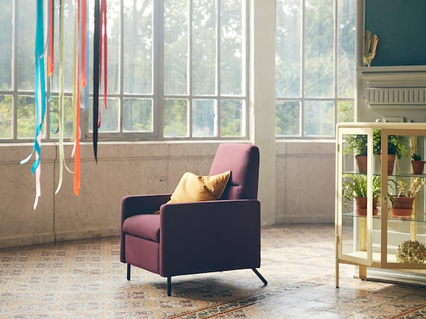 GISTAD recliner in a dark red colour with a yellow cushion placed in its seat, standing in a room with big windows.
