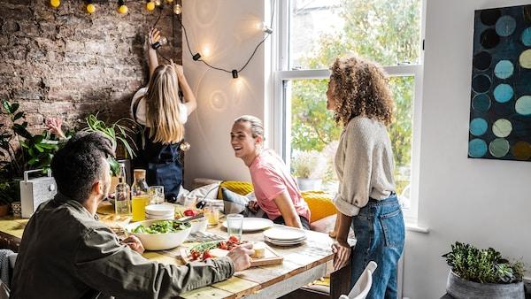 Glade mennesker omkring et spisebord med mad på bordet.