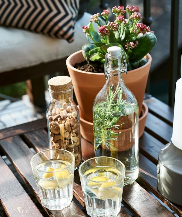Glas, karaffel og urtepotteskjuler på en havebænk af træ.