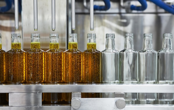 Glass bottles being filled with oil on a production line.