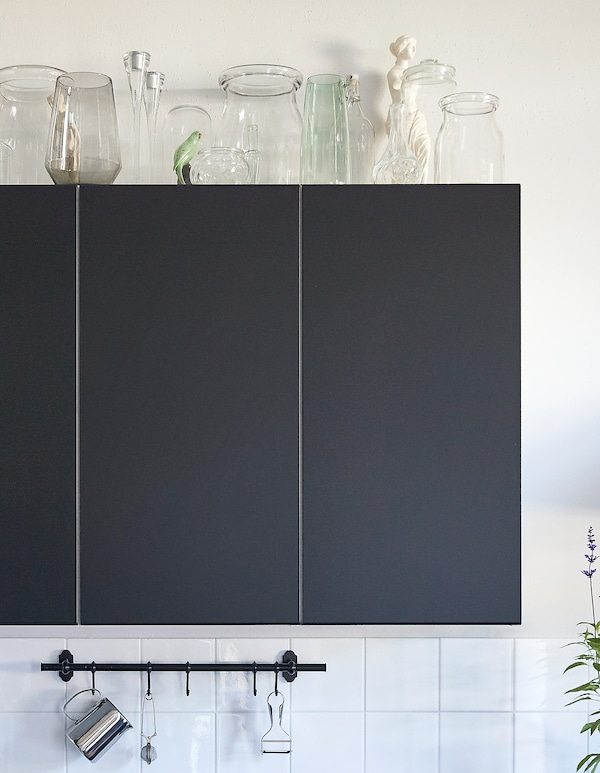 Glass jars, candlesticks and vases arranged on top of black kitchen wall units.