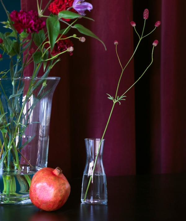 Glass vases with simple flower arrangements shown against a deep rich red curtain.