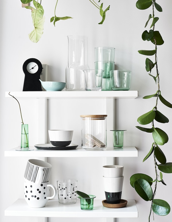 Glasses, mugs and plant cuttings displayed on three white shelves.