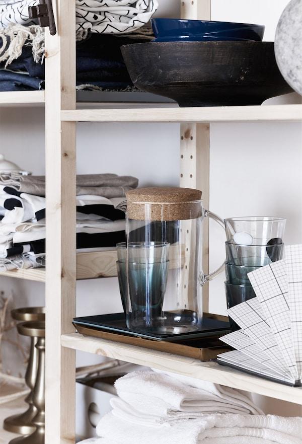 Glassware and ceramics on open shelves.