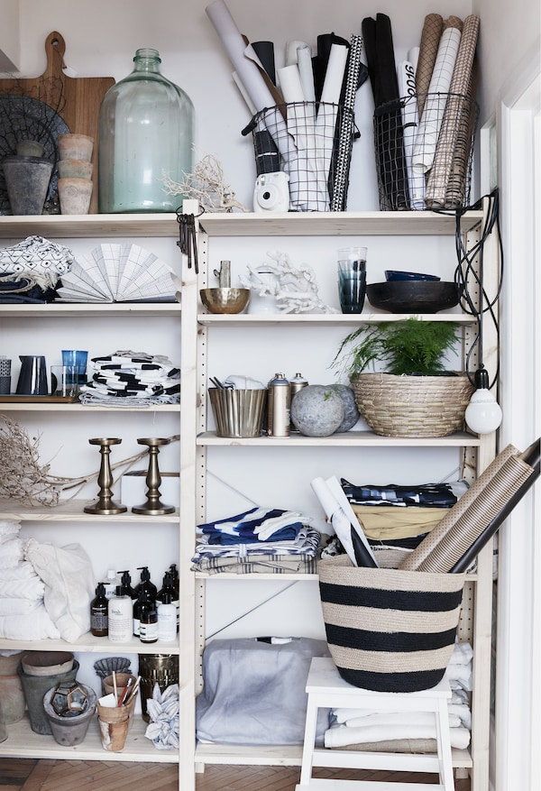 Glassware, textiles and plants on open shelves.