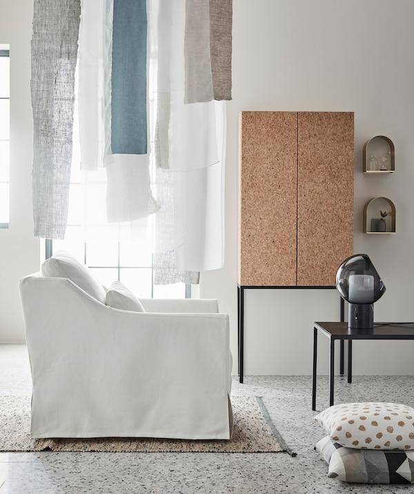 Gleitende Stoffe, sanfte Farben, Möbel mit dünner Linienführung: Sie alle leiten das Tageslicht und schenken dem Raum ein ruhiges, luftiges Ambiente, u. a. mit SAMMANHANG Schrank Kork.